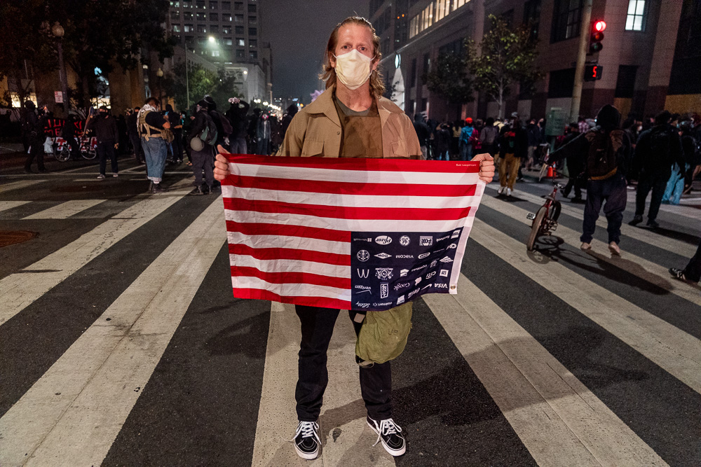 Ryan Miller poses for a photo at the 'Justice for Jacob' protest near the U.S. District Courthouse in Oakland, Calif., August 26, 2020. Just before several protesters went onto federal property to hit a door at the courthouse and were met with pepper ball fire from unknown officers.