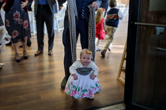A small child, just learning to walk, waddles toward the photographer. Around her waist is a long checkered scarf, either end of which is held by her father, who is using it to help support her.