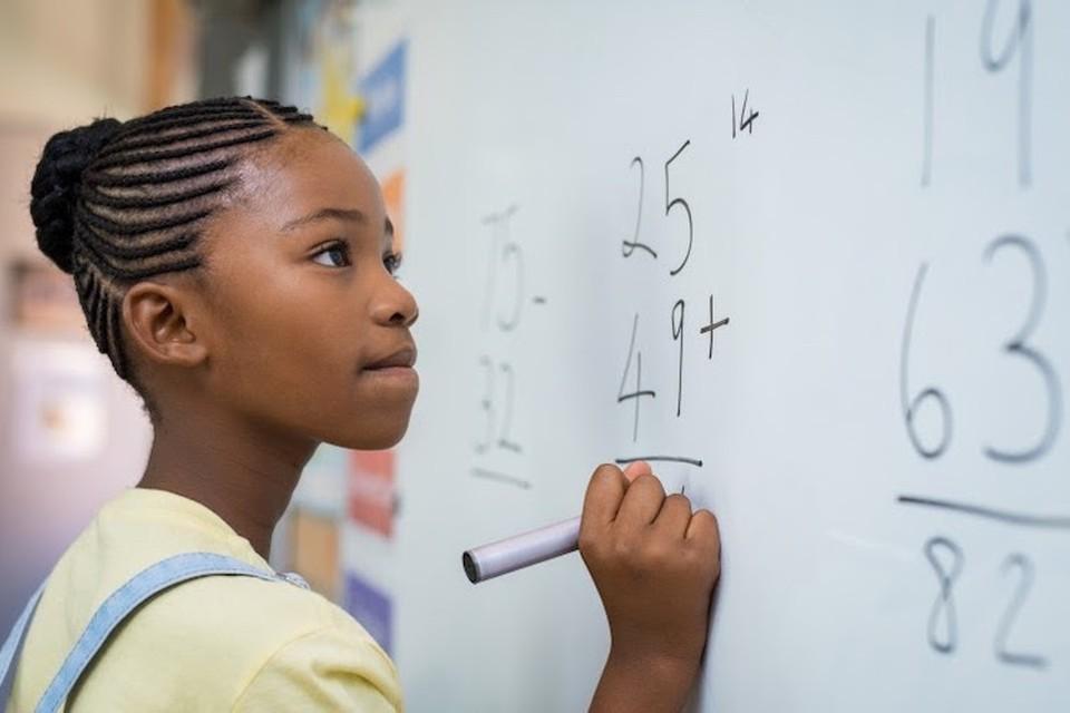 Student solves math problem on whiteboard.