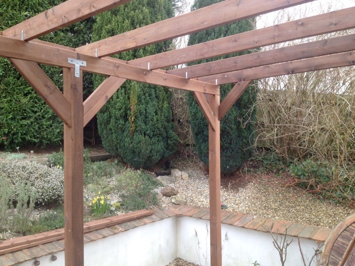 A pergola constructed in front of a small treeline, stained with a walnut-brown wood stain