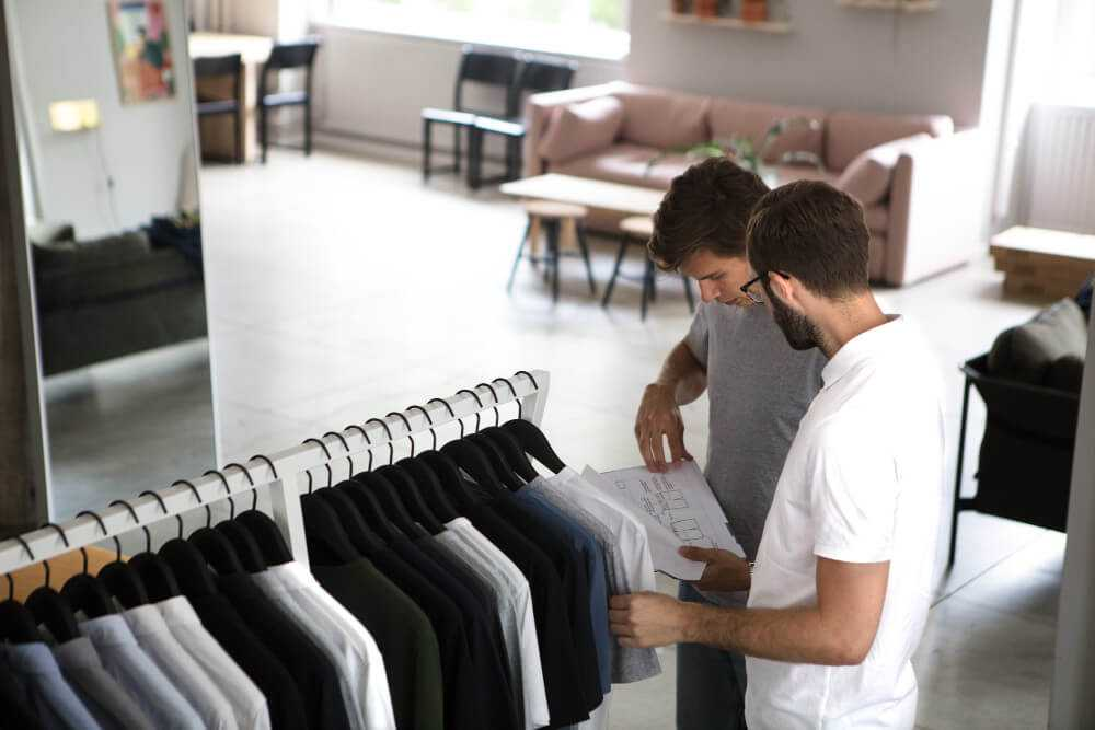 Asket founders August and Jakob checking clothes on the rack