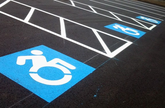 blacktop parking spaces with the updated, forward leaning wheelchair accessible icons painted in each space