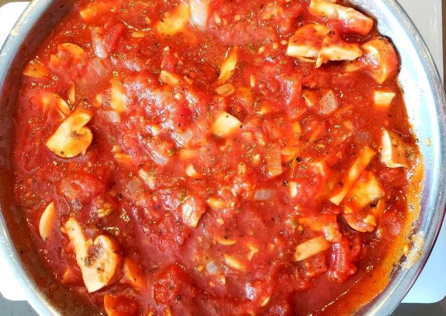 Bowl of tomato sauce with onion and mushrooms