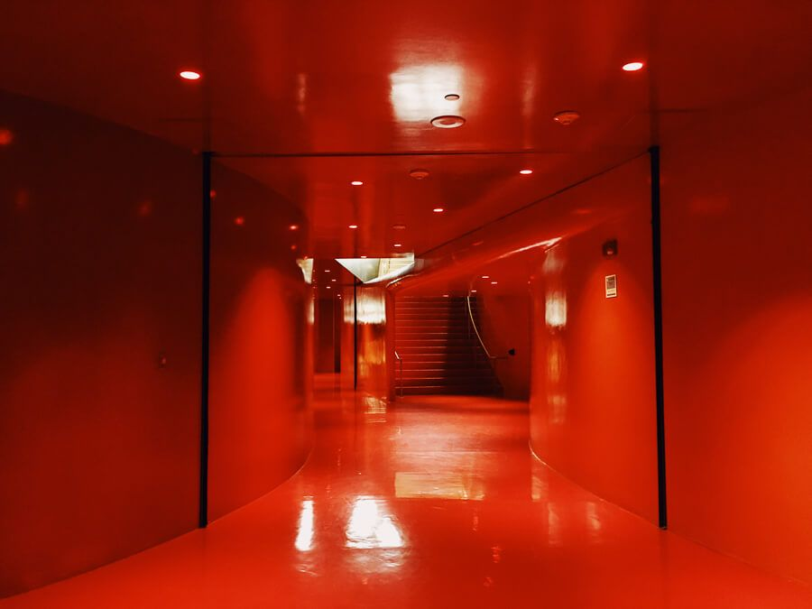 Down an empty allway that's painted from floor to ceiling red