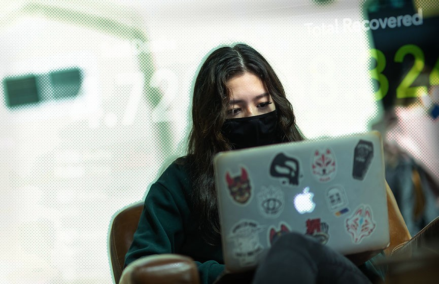 A young adult wearing a mask participates in an online COVID-19 survey