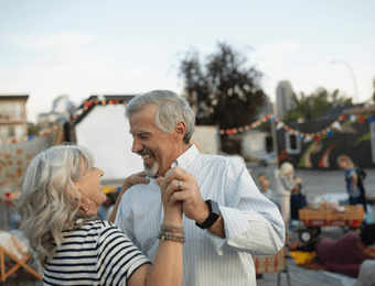 Elderly couple dancing outside.