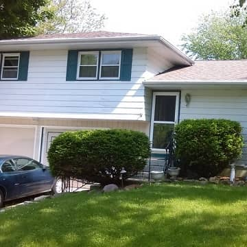 before picture of a brown home being painted dark grey