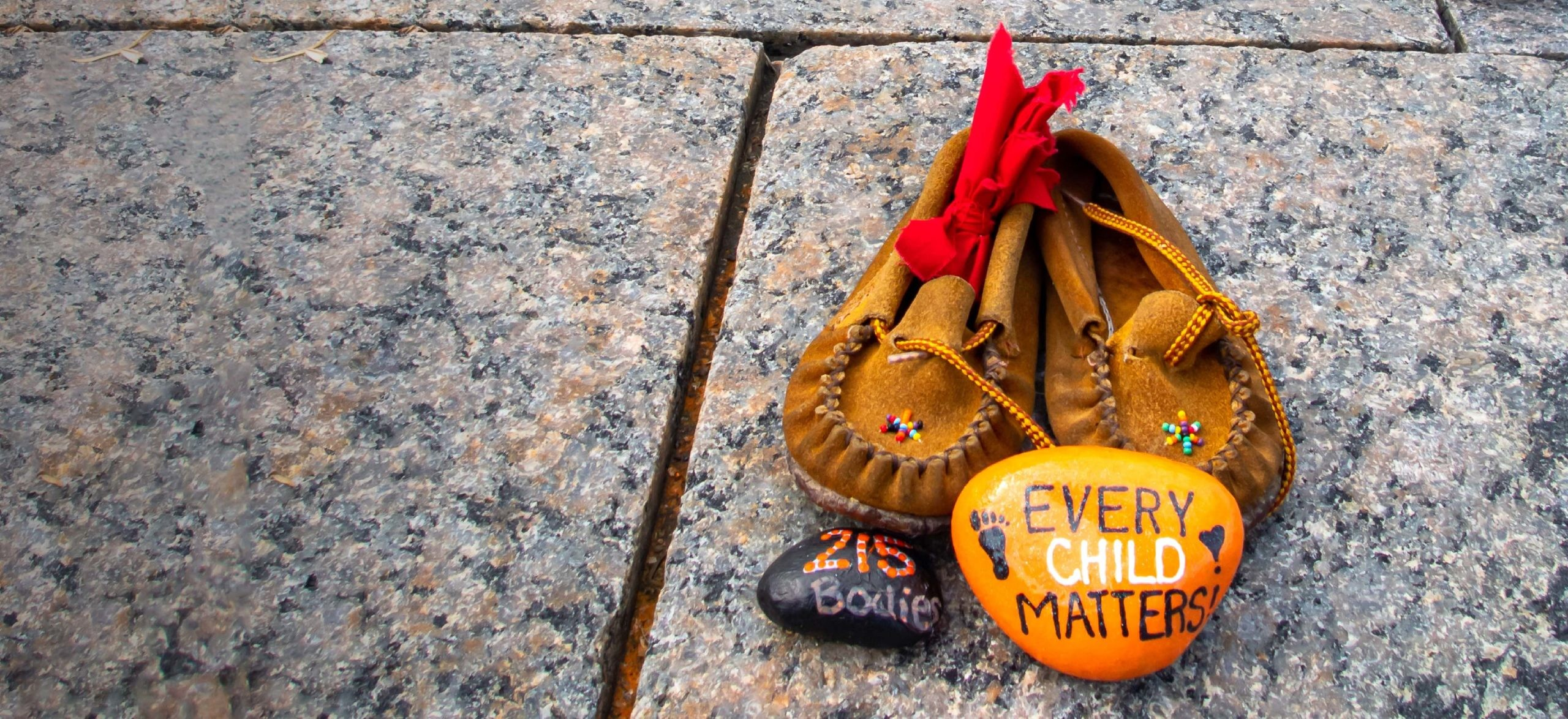 """Children's shoes and a painted orange rock that reads """"Every Child Matters"""" site at a memorial at Canada's Parliament Hill for Indigenous children who were sent to residential schools"""