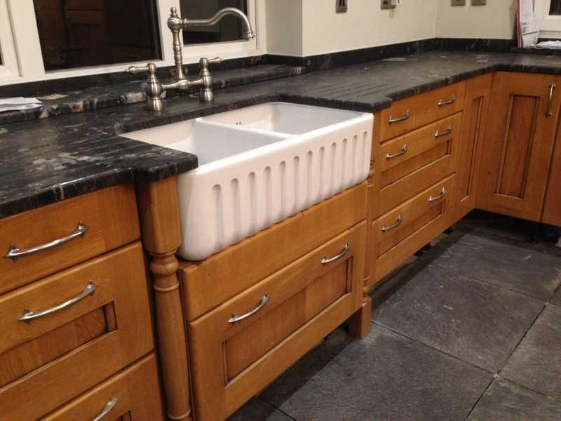 New belfast sink set within a granite worktop, with oak kitchen doors either side