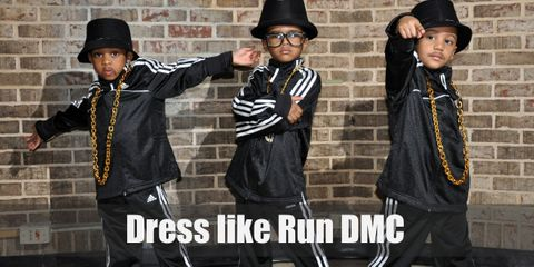 One thing Run DMC definitely changed is the hip hop fashion, and they're influence is still rampant 28 years later. For this outfit, they're wearing trademark black Adidas tracksuits and sneakers, their gold blings, and bucket hats.