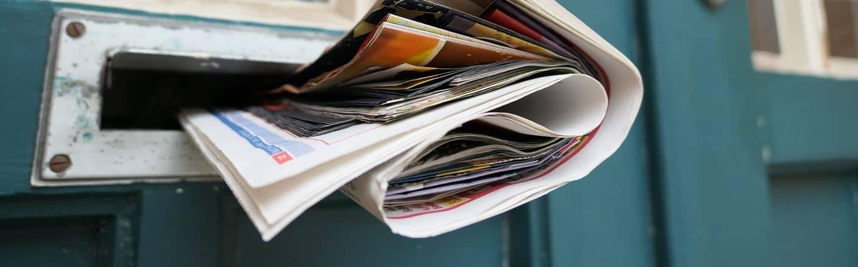 Zeitung die aus Zeitungsschlitz bei blauer Holztuer guckt