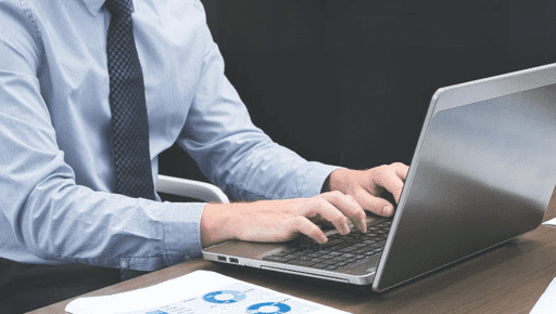 Man in blue shirt and tie sits at wooden desk and types on grey laptop next to reports and files to create a beautiful financial report for his accounting clients with Futrli as an accountant #reporting
