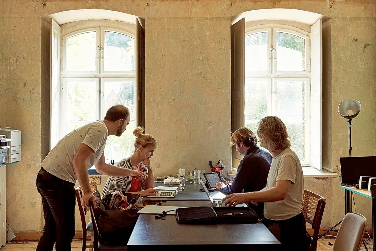 Menschen die gemeinsam an einem Tisch arbeiten