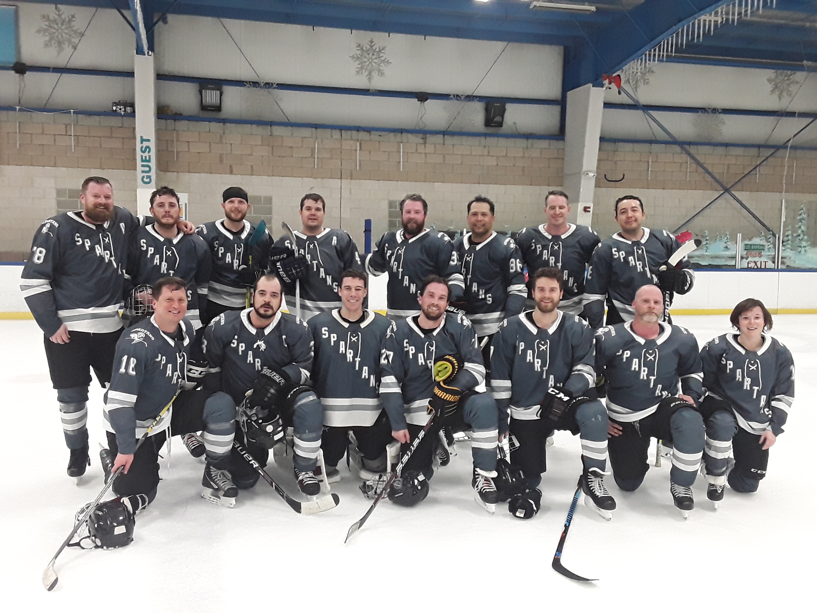A hockey team posing for a picture on the ice