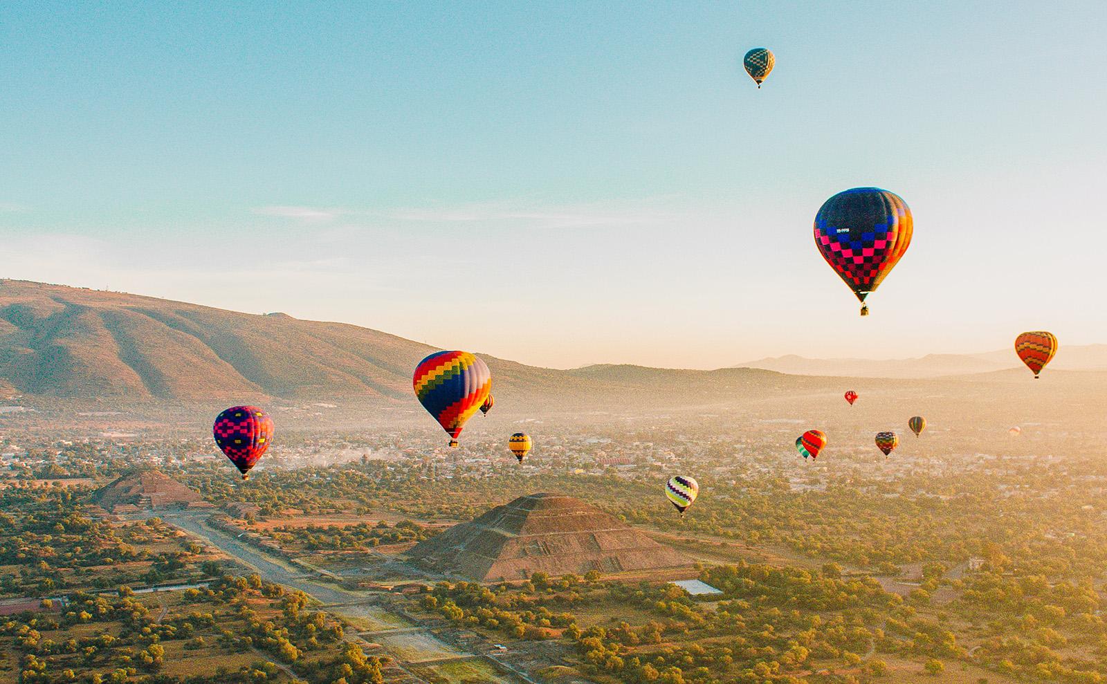 hot air balloons floating over Mayan pyramids