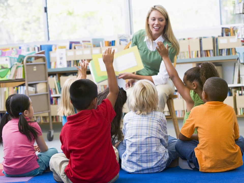 Teacher reads to elementary students in a library.
