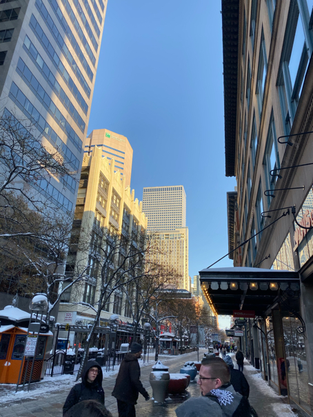 A view of downtown Denver on 16th Street with all the tall buildings and people walking around on a cold day after three days of snow.
