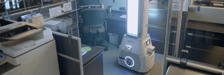 Robot désinfectant en action dans un cubicule de travail.