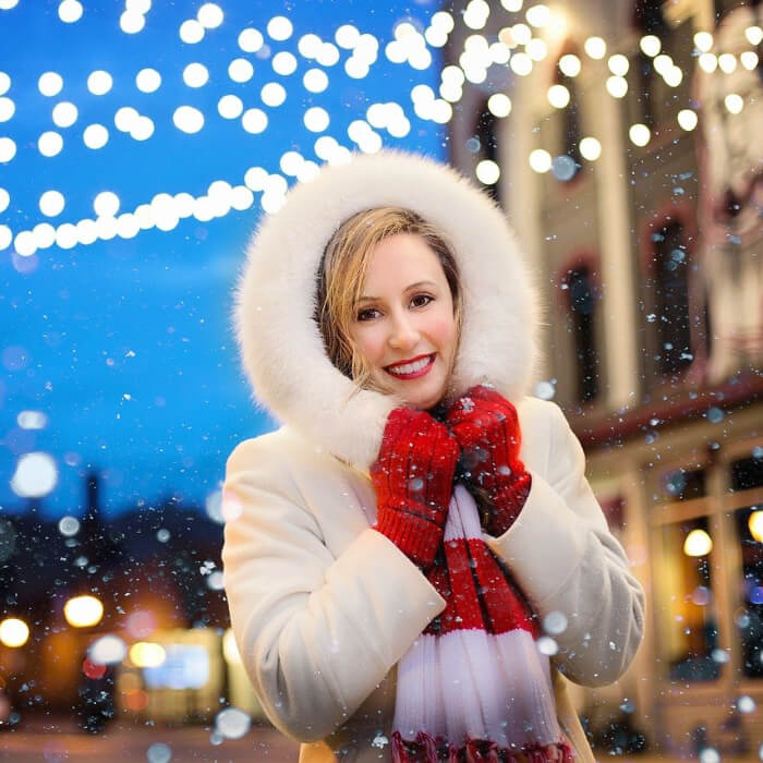 Woman under snow and lights.