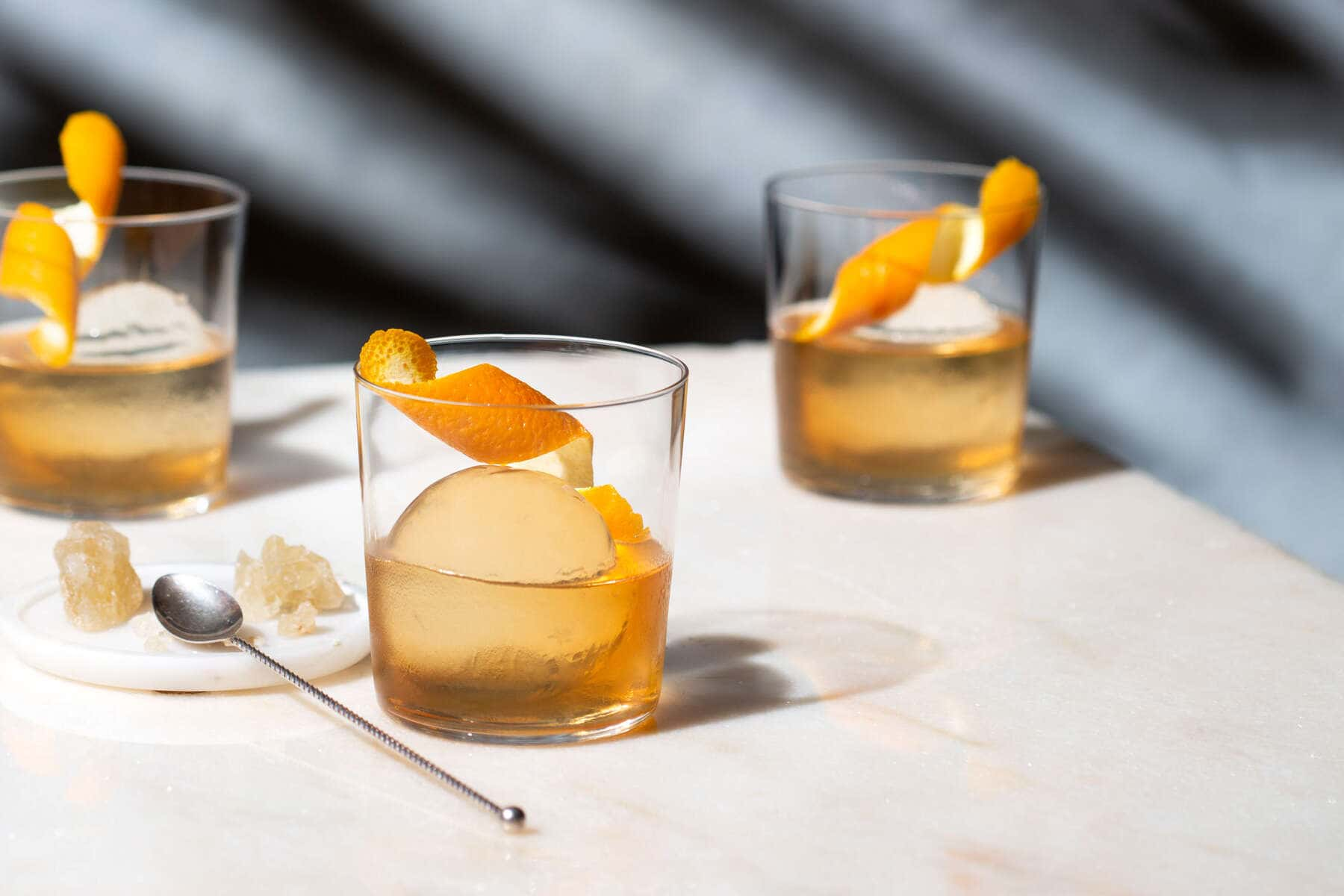 old fashioned cocktail with rock sugar and orange