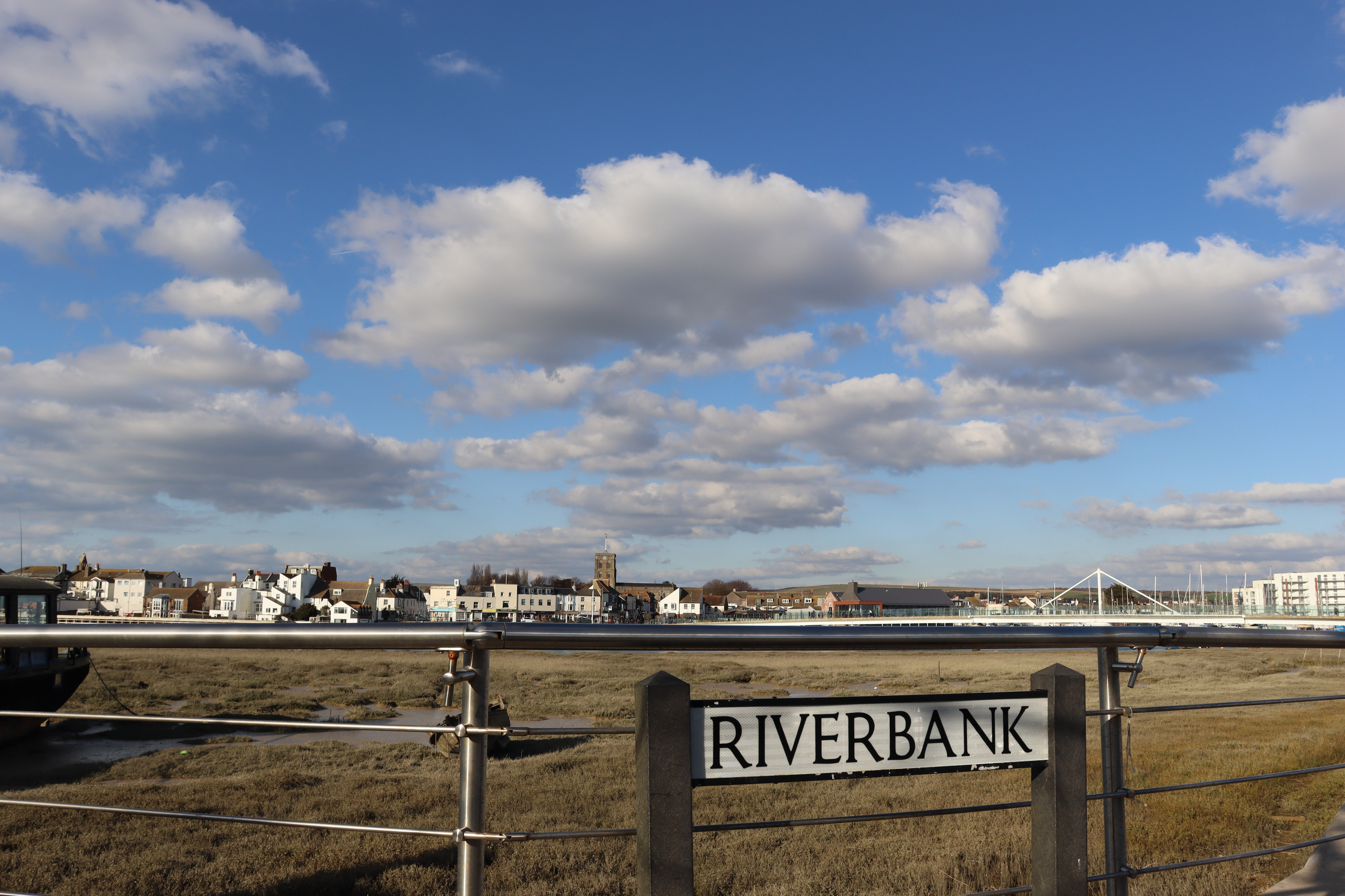"""A street sign saying """"Riverbank"""" in front of some silver railings overlooking the river and the town of Shoreham-by-Sea on the other side of the river."""