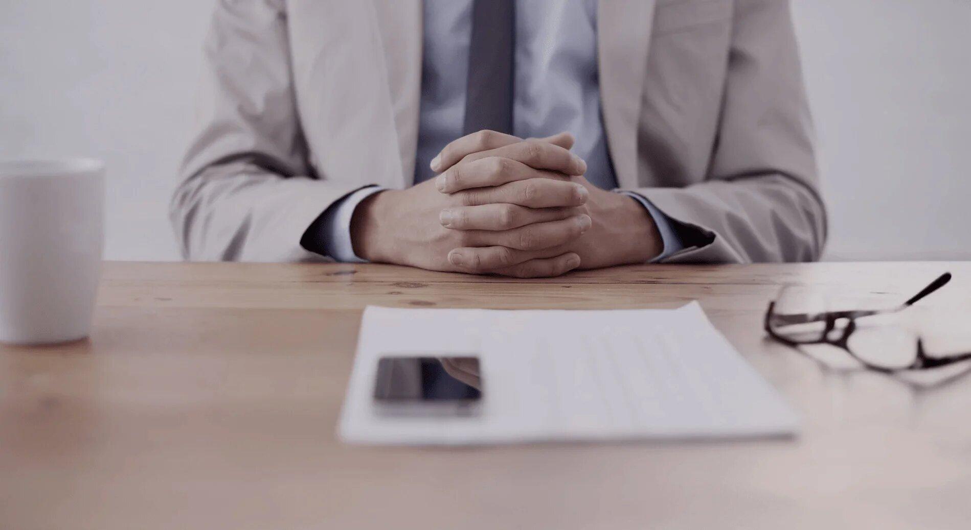 Doctor sitting across desk preparing for consultation