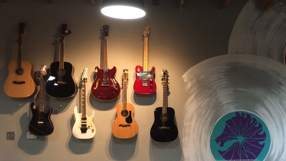 Back wall of Brothers Music with guitars hanging and a mural of a record