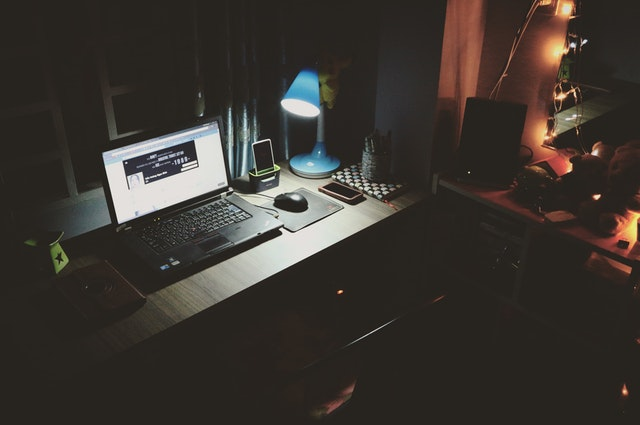 Empty desk in the dark with a single lamp