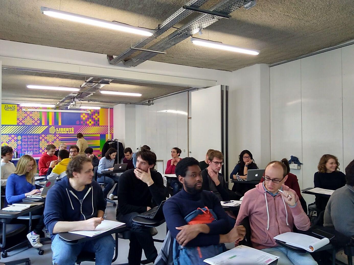 Dans une grande salle, les EIG de la promotion 2 sont assis à des pupitres individuels et discutent entre eux.