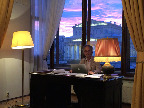author Amor Towles sitting at a desk in his room at the Metropol