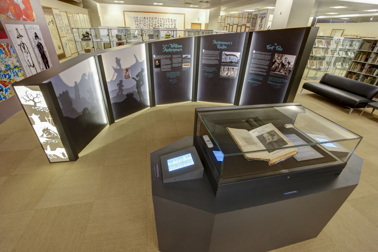 A photo overview of the exhibition. The First Folio lies in the showcase in the middle, surrounded by informational walls. Some walls are also decorated in silhouette art.