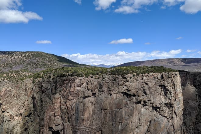 Looking straight across the Black Canyon of the Gunnison to the north rim's high plateau. In the distance, ramed by two low, wide hills, can be seen a range of domed, snow-capped mountains.