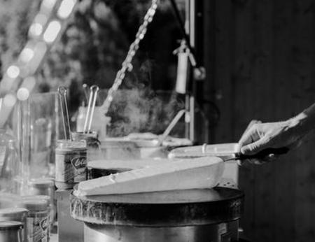 Schwarz-Weiß Foto eines Crêpes, der über einer Crepes Platte gewendet wird