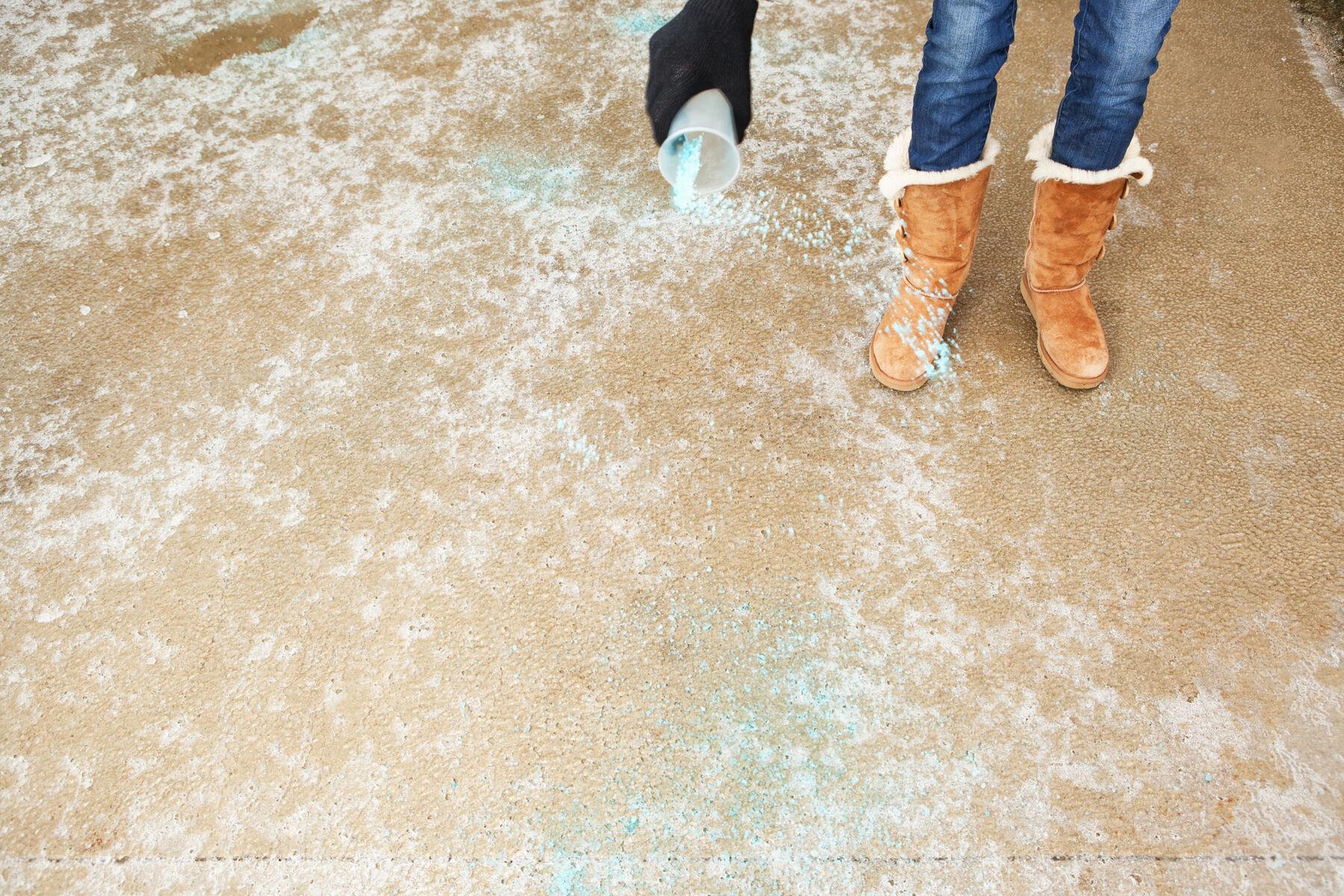 a woman is spreading blue rock salt on a frozen winter driveway