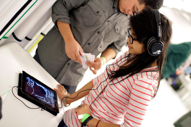 A woman wears headphones and focuses on the sounds of the non-visual game.