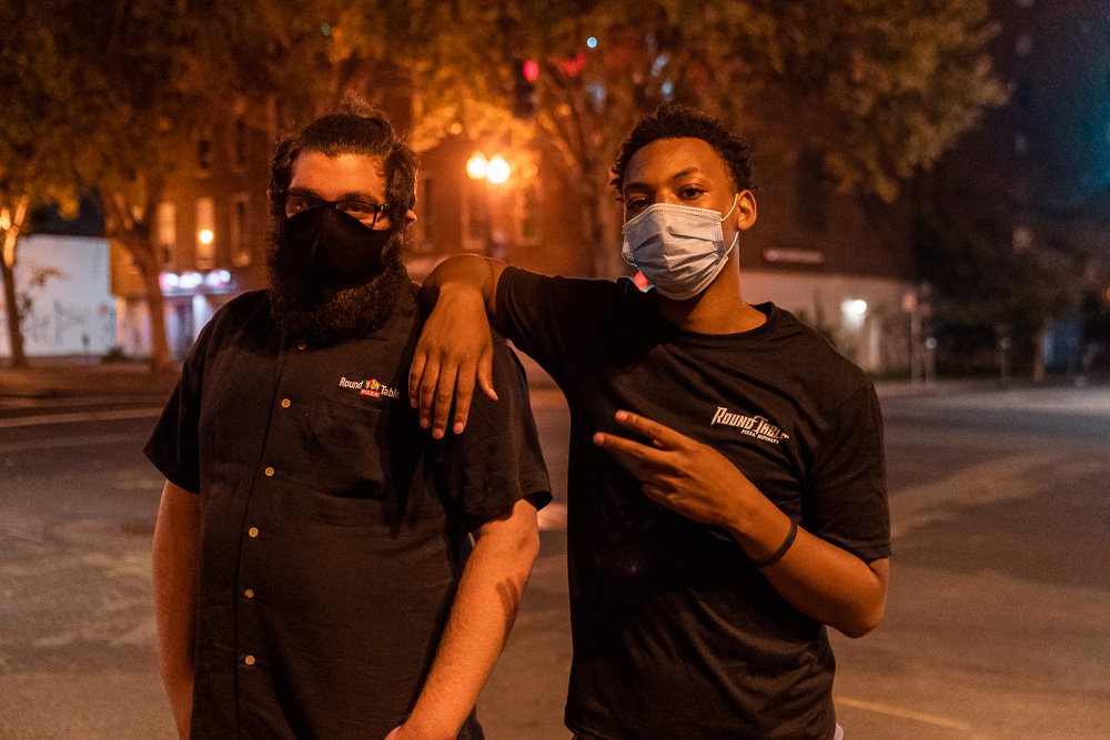 Nyjis Coleman (right) and a co-worker pose for a photo outside Round Table Pizza on Grand Avenue in Oakland, Calif., August 26, 2020. People protesting against the police shooting of Jacob Black in Kenosha, Wis. moved the restaurant's dumpsters into the street to slow down police. Employees came out to retrieve the dumpsters after the protest had left the area.