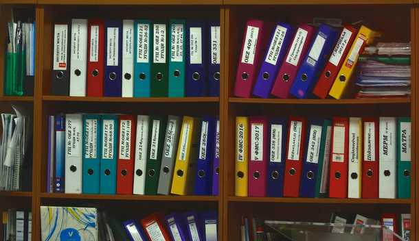 Binders and papers on shelf