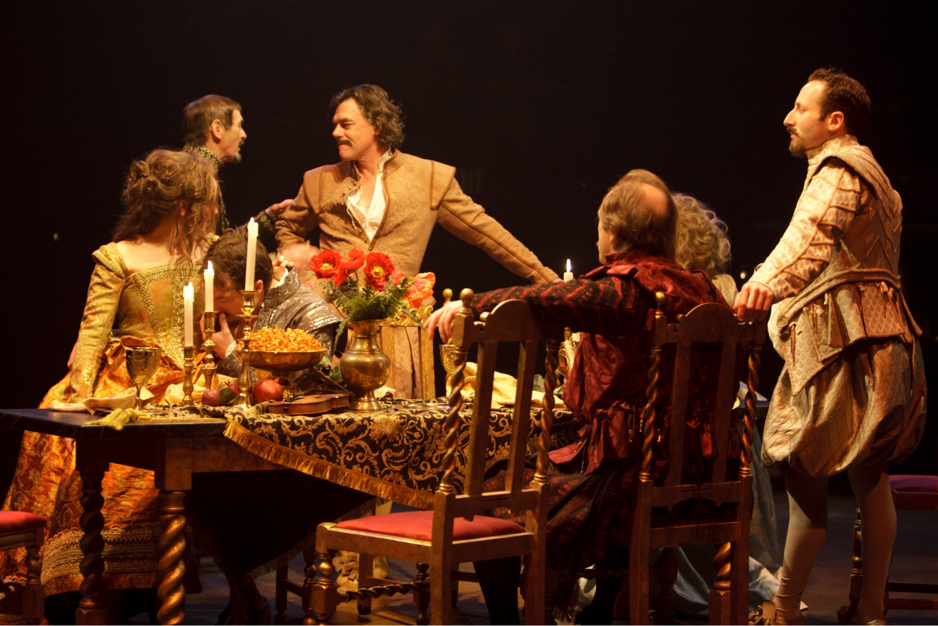 Seven people in fancy attire gathered for elaborate candle-lit dinner.