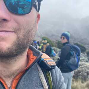 Dan Furze, close up, reflection in blue sunglass, on a hike.