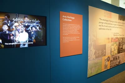 A close-up of the Arts Heritage introduction wall. A TV is showing a video with a concert performance.