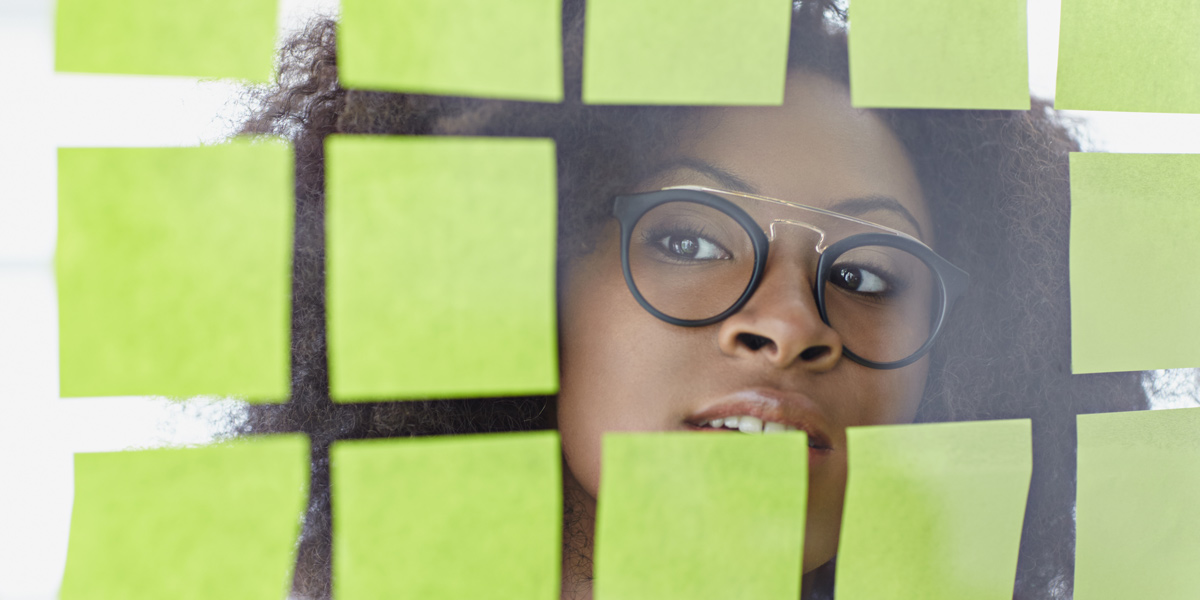 A UX designer peeking through a glass wall, surrounded by Post-It notes