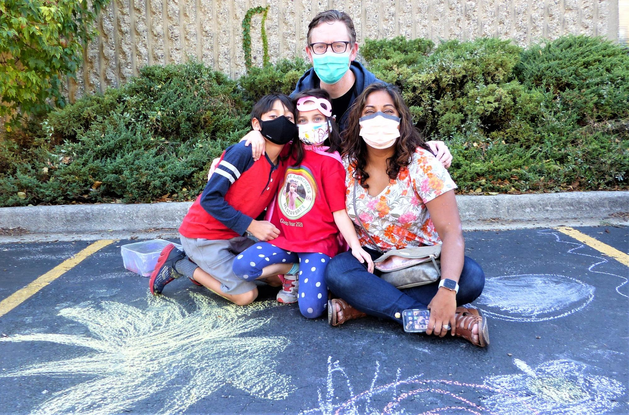 Four community members outside with chalk art.