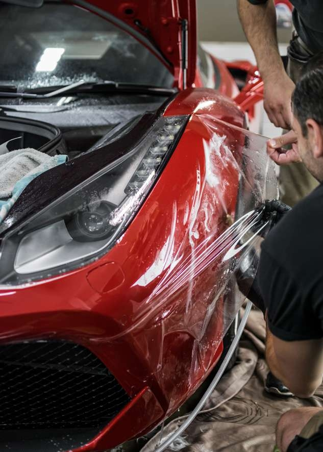 Paint protection film (PPF) being applied to red Ferrari 458 GTB front bumper