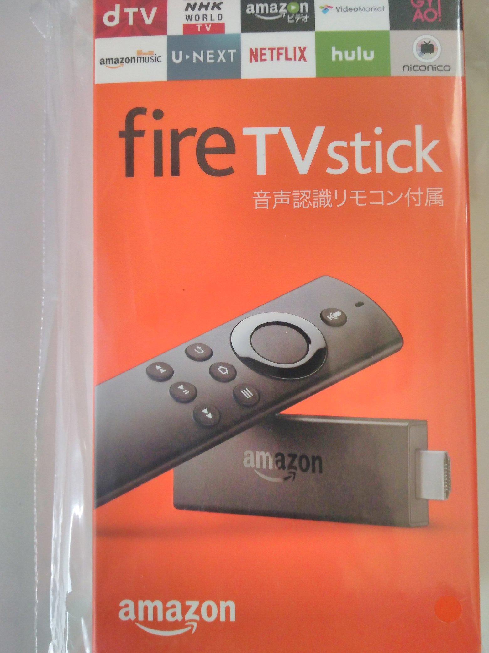 Fire TV Stickのオレンジ色の外箱。パッケージには立てられたFire TV Stickによりかかるようにそのリモコンが乗っている構図の写真です。