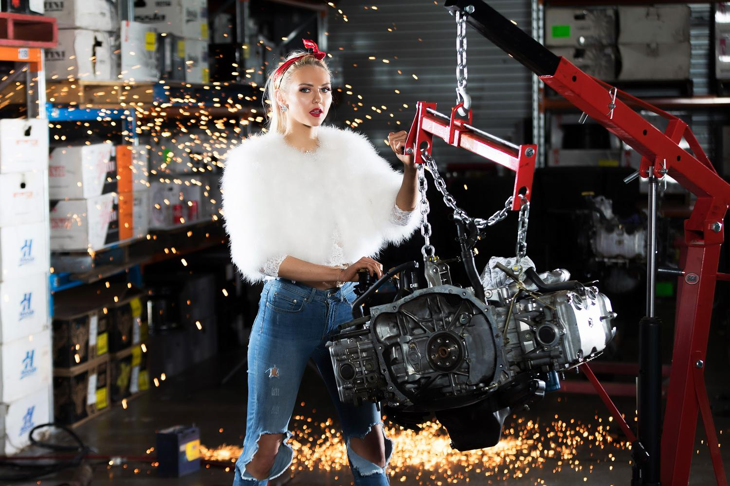Women posing with car engine in garage