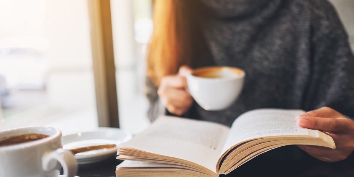 Close up of someone in a grey sweater reading a book and drinking coffee