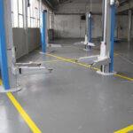 Pavimento in resina in un'officina meccanica di Treviso, munita di trattamento anti statico e segnaletica orizzontale.