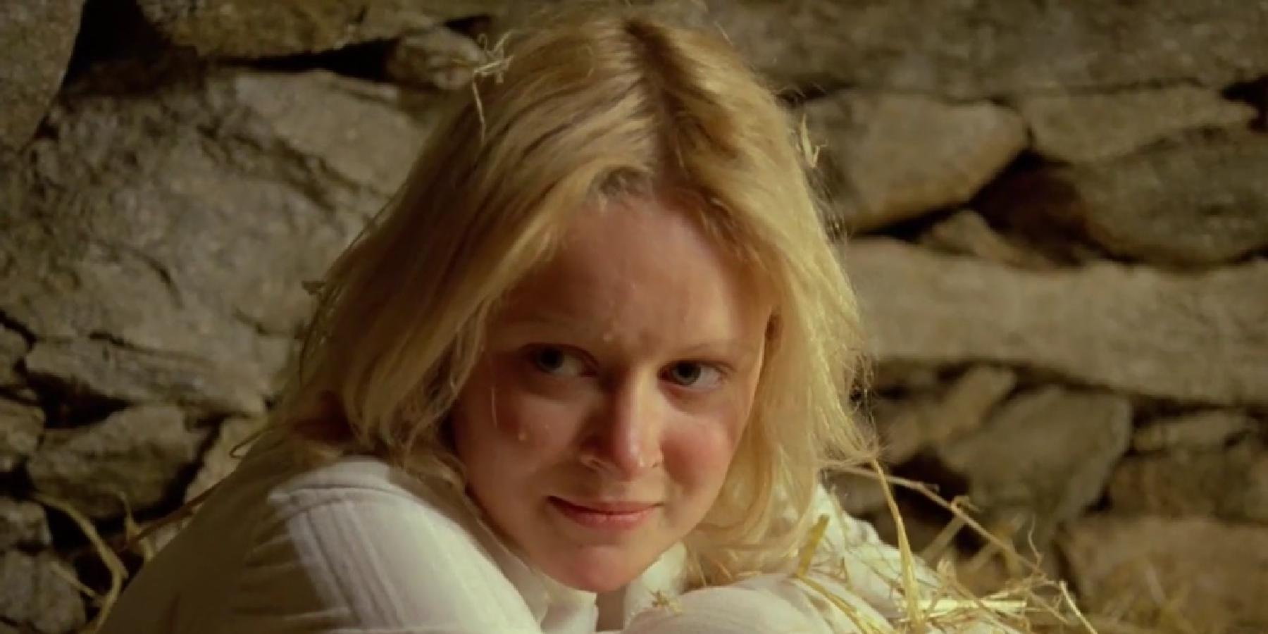Lead actress Jane Lyle in a still from the movie Island of Death. She is hugging her knees to her shoulders, looking slightly off camera with an expression of schadenfreude.
