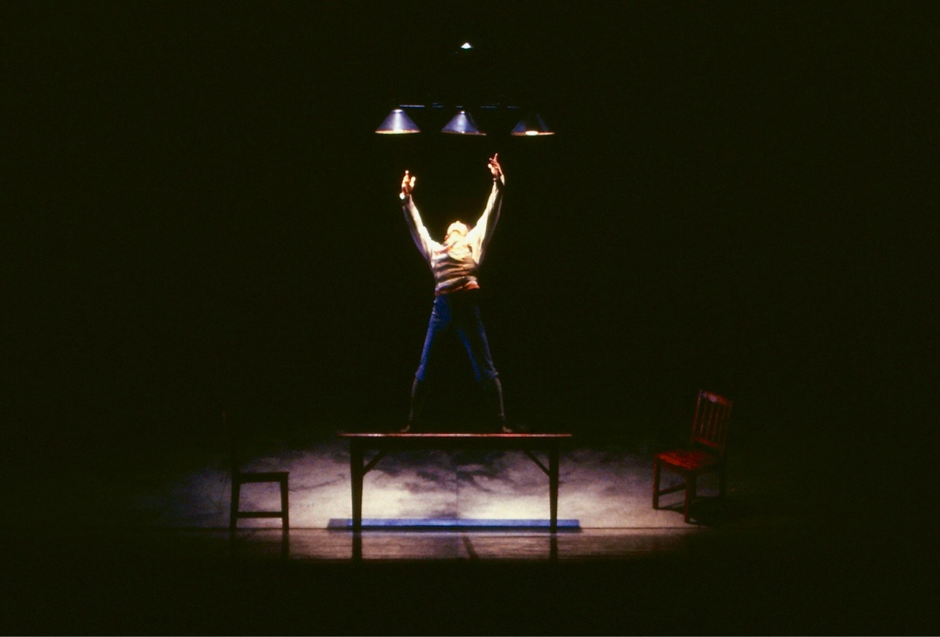 Dancer in schoolboy attire stands on table extending arms to overhead lamps, in front of chair on raked platform.