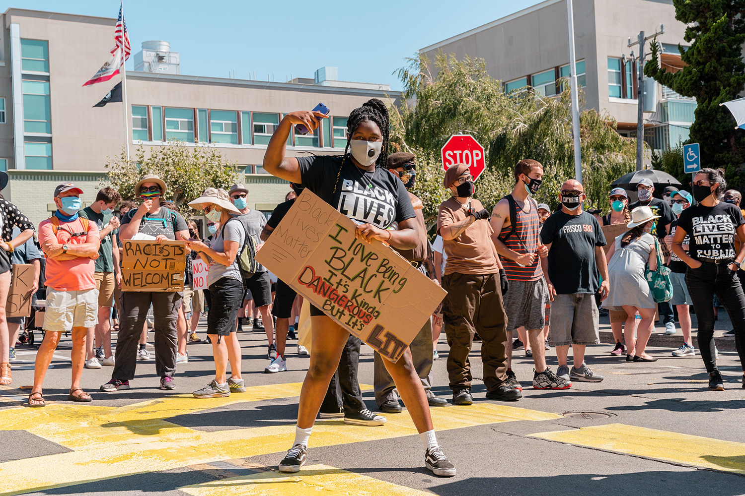 "A protestor poses with a sign in front of the Contra Costa County Courthouse at the ""Zero Tolerance for White Supremacy"" protest in Martinez, Calif., on Sunday, July 12, 2020. ""Black Lives Matter"" was painted in large letters on the road in front of the courthouse with permission from the city — it was later vandalized by a couple who partially painted over it. They were eventually arrested, but won praise from Tucker Carlson for the act."